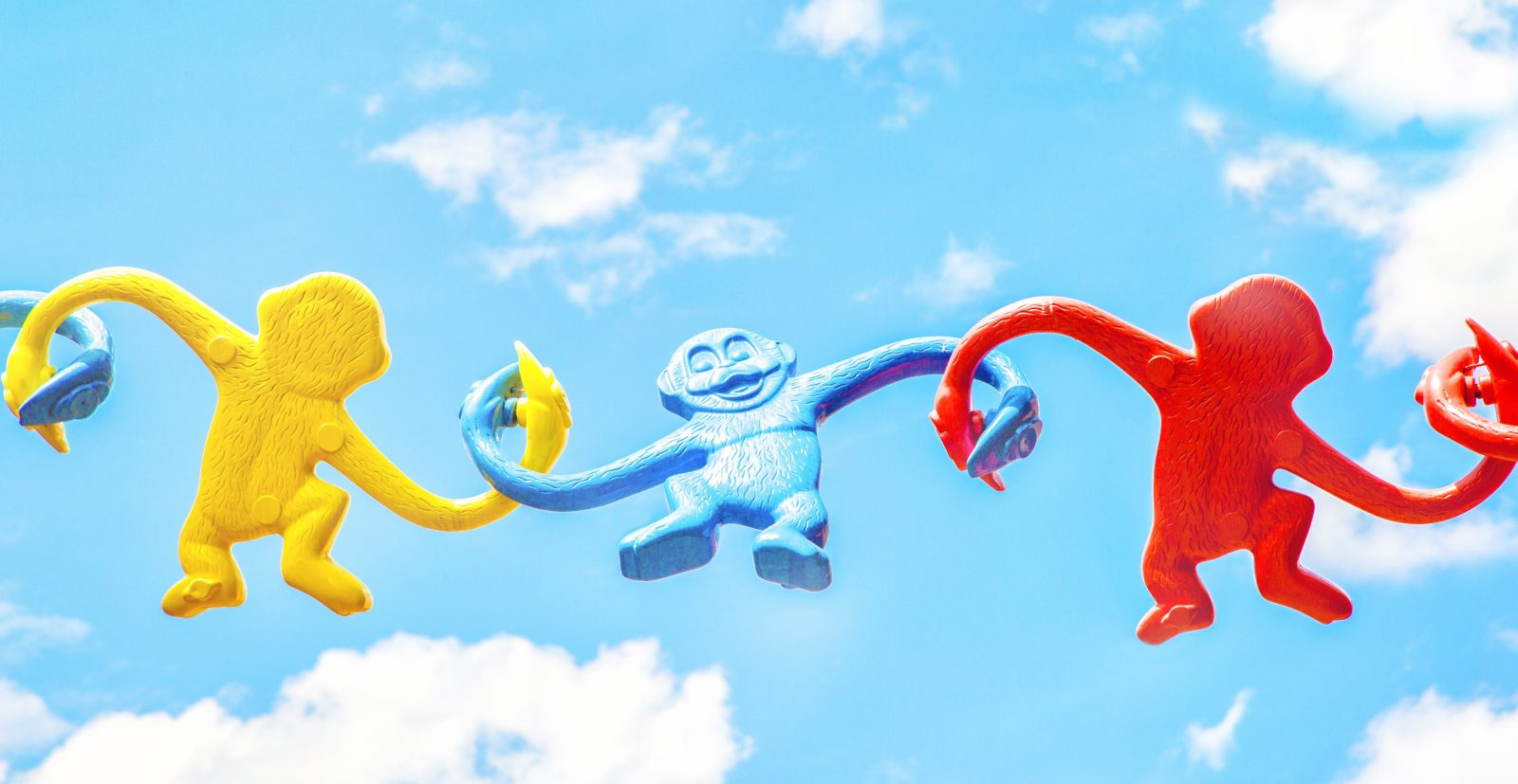 yellow, blue and red plastic monkeys holding hands across a blue sky