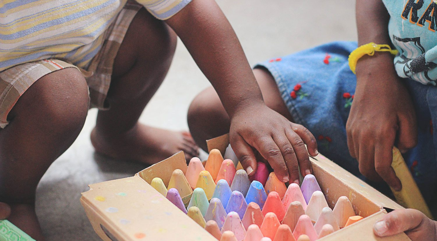 box of chalk crayons with two children crouching around them. their faces are not in the image.