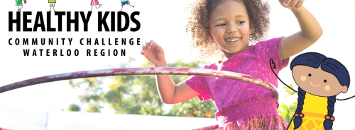 young girl in a purple dress with a hulahoop and the healthy kids community challenge logo to the left