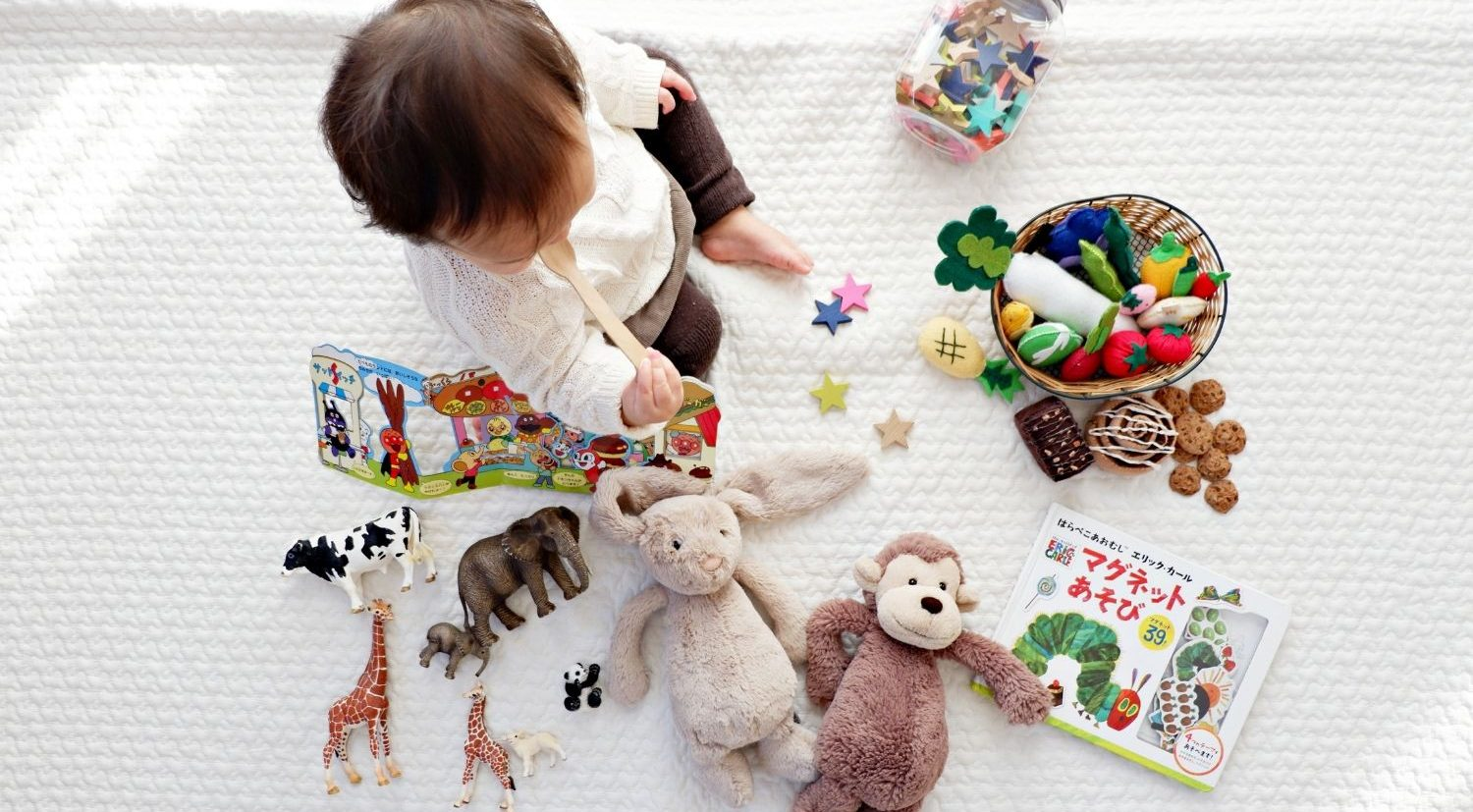 image of toddler playing with toys on a white background